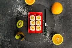 Les petits pains de sushi ont complété avec de la sauce douce d'un plat en pierre, vue à partir du dessus photographie stock