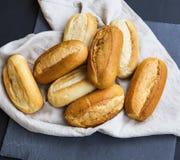Les petits pains fraîchement cuits au four de pain sur une serviette de toile, des petits pains de pain entier amassent Photographie stock