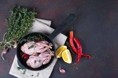 Les petits quals crus avec certains épicent prêt pour faire cuire sur la casserole ronde Photographie stock