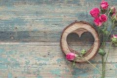Les petits roses et coeur ont découpé en bois sur le vieux grunge peint Images libres de droits