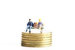 Les peuples miniatures s'asseyent sur des pièces de monnaie Photographie stock