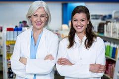 Les pharmaciens de sourire se tenant avec des bras ont croisé dans la pharmacie Photographie stock libre de droits