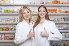 Les pharmaciens tiennent leurs pouces dans la pharmacie Photographie stock libre de droits