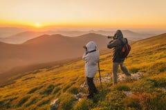 Les photographes prend un coucher du soleil dans les montagnes photos stock