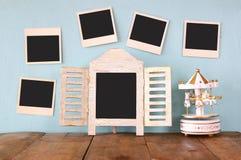 Les photos instantanées vides accrochent au-dessus du fond texturisé en bois à côté des chevaux blancs vides de tableau noir et d Photos stock