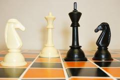Les pièces d'échecs blanches et noires sur le jeu embarquent Photos libres de droits