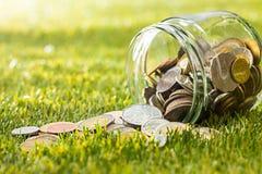Les pièces de monnaie au pot en verre pour l'argent sur l'herbe verte Images stock