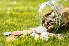 Les pièces de monnaie au pot en verre pour l'argent sur l'herbe verte Photographie stock