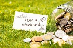 Les pièces de monnaie au pot en verre pour l'argent sur l'herbe verte Photos libres de droits