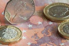 Les pièces de monnaie britanniques ont placé sur un billet de banque de l'euro Dix Photos stock