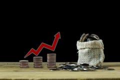 Les pièces de monnaie débordent du sac à chanvre et empilent la pièce de monnaie avec la flèche rouge sur la table en bois Image libre de droits