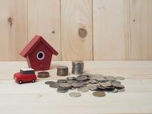 Les pièces de monnaie d'argent empilent l'élevage avec la maison rouge sur le fond en bois Photo stock