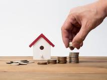 Les pièces de monnaie d'argent empilent l'élevage avec la maison rouge sur le fond en bois Photos stock