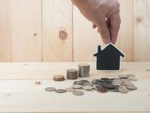 Les pièces de monnaie d'argent empilent l'élevage avec la maison rouge sur le fond en bois bus Photo stock