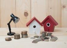 Les pièces de monnaie d'argent empilent l'élevage avec la maison rouge sur le fond en bois bus Images libres de droits