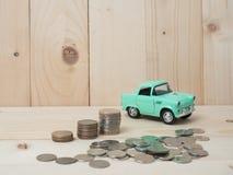 les pièces de monnaie d'oney empilent l'élevage avec la voiture verte sur le fond en bois Busi Images stock