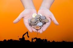 Les pièces de monnaie dans des mains sur la silhouette d'industrie aménagent le fond en parc, charité d'aide financière de fonds  Photos stock
