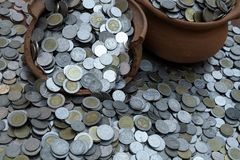 Les pièces de monnaie dans le pot cassé de sur des sorts de pile inventent avec le fond brouillé, la pile d'argent pour l'investi images libres de droits