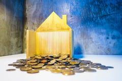 Les pièces de monnaie dans les maisons en bois là sont beaucoup inventent et la feuille d'arbres se développent Sav Photos stock
