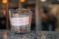 Les pièces de monnaie dans un récipient en verre avec un label encaissent Photographie stock libre de droits