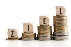 Les pièces de monnaie empilées montrant un graphique croissant avec des cubes et le ` allemand de mot visent le ` Images libres de droits