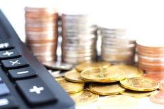 Les pièces de monnaie empilent avec une calculatrice sur le fond blanc Images stock