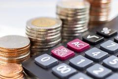 Les pièces de monnaie empilent avec une calculatrice sur le fond blanc Photo libre de droits