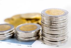 Les pièces de monnaie empilent sur le fond blanc Photos stock