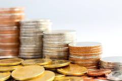 Les pièces de monnaie empilent sur le fond blanc Photos libres de droits
