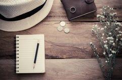 Les pièces de monnaie et la fleur de portefeuille de chapeau de crayon de carnet sur la table en bois - modifiez la tonalité le v photos stock