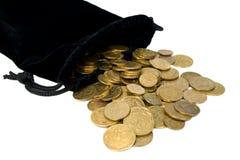 Les pièces de monnaie ont débordé le sac. Photos stock