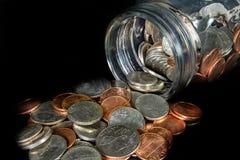 Les pièces de monnaie ont débordé un pot de maçon sur le fond noir photo libre de droits
