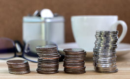Les pièces de monnaie ont empilé l'élevage avec les verres et la tasse de café sur la table en bois Photo libre de droits
