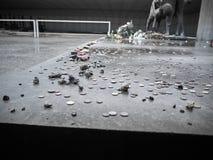 Les pièces de monnaie ont mis près d'une statue commémorative dans le souvenir des victimes image libre de droits