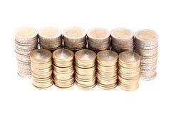 Les pièces de monnaie organisées dans les fléaux et les lignes ont isolé image stock