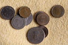 Les pièces de monnaie taiwanaises du dollar ont dispersé sur une surface jaune Photo stock
