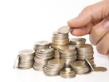 Les pièces de monnaie de Turkishish ont aligné dans une rangée sur un fond blanc et cela s'ajoutant dessus des mains photo libre de droits