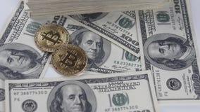 Les pièces du bitcoin BTC tombent sur les billets des dollars américains dans le mouvement lent banque de vidéos