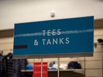 Les pièces en t et les chemises de réservoirs signent accrocher dans le magasin photo stock