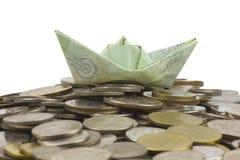 Les pièces et le billet de devise de la Thaïlande ont plié à l'origami le voilier sur le fond blanc avec le chemin cipping image stock