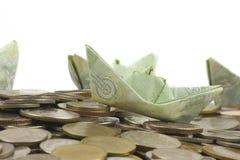 Les pièces et le billet de devise de la Thaïlande ont plié à l'origami le voilier sur le fond blanc avec le chemin cipping images libres de droits