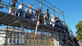 les Piéton-touristes sont en voyages de jour au pont pour croiser l'itinéraire du marathon à St Petersburg banque de vidéos