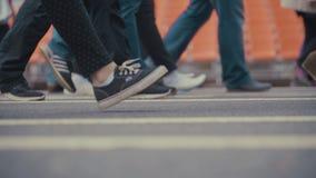 Les piétonnes de personnes marche à travers une rue occupée de ville Images stock