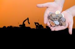 Les pièces de monnaie dans des mains sur la silhouette d'industrie aménagent le fond en parc Photographie stock