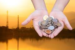Les pièces de monnaie dans des mains sur la silhouette d'industrie aménagent le fond en parc Image stock