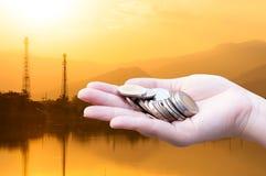 Les pièces de monnaie dans des mains sur la silhouette d'industrie aménagent le fond en parc, charité d'aide financière de fonds  Images stock