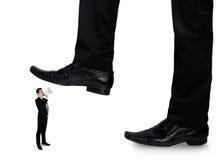 Les pieds équipent écraser peu d'homme d'affaires Photographie stock