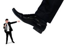 Les pieds équipent écraser peu d'homme d'affaires Photo stock
