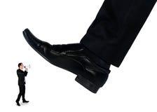 Les pieds équipent écraser peu d'homme d'affaires Photographie stock libre de droits