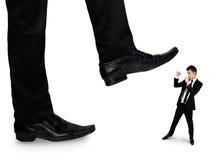 Les pieds équipent écraser peu d'homme d'affaires Image stock